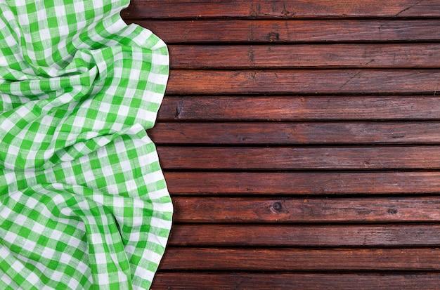 Nappe à carreaux vert sur table en bois foncé