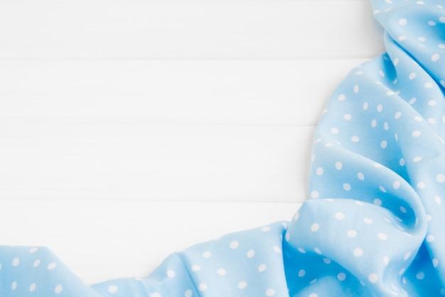 Nappe pliée à pois bleu clair sur une table en bois blanchie.