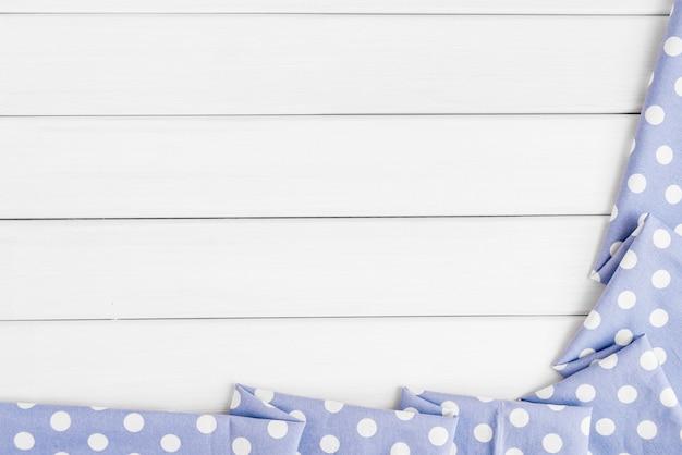Nappe pliée à pois bleu violet clair sur une table en bois blanchi.
