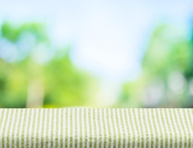 Nappe de rayures vertes vides avec soleil et flou arbre vert
