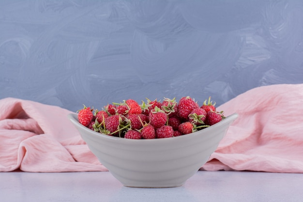 Nappe rose derrière un bol de framboises sur fond de marbre. photo de haute qualité