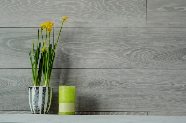 Narcisse dans un pot de fleurs et une bougie verte sur un fond de mur en bois. espace pour le texte.