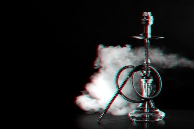 Narguilé avec des charbons et de la fumée sur la table dans un restaurant