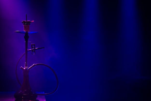 Le narguilé classique avec des rayons colorés de lumière et de fumée.