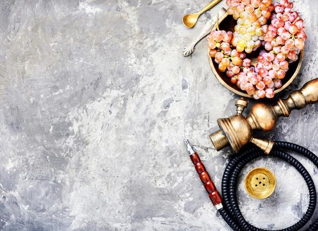 Narguilé avec des raisins arômes sur fond de béton