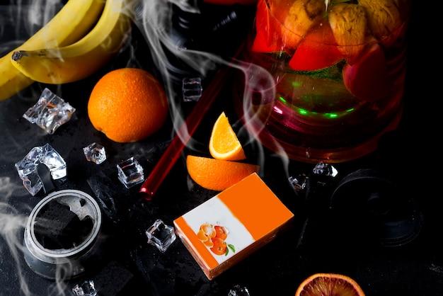 Narguilé rouge à l'orange et avec une boîte de tabac
