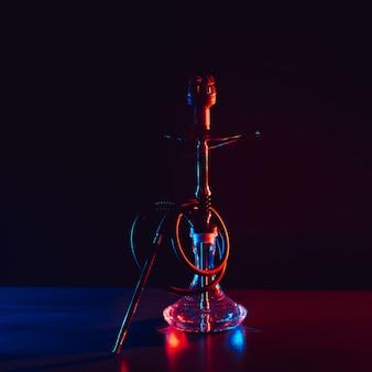 Narguilé en verre avec un bol en métal avec des charbons ardents sur fond noir sur une table dans un restaurant