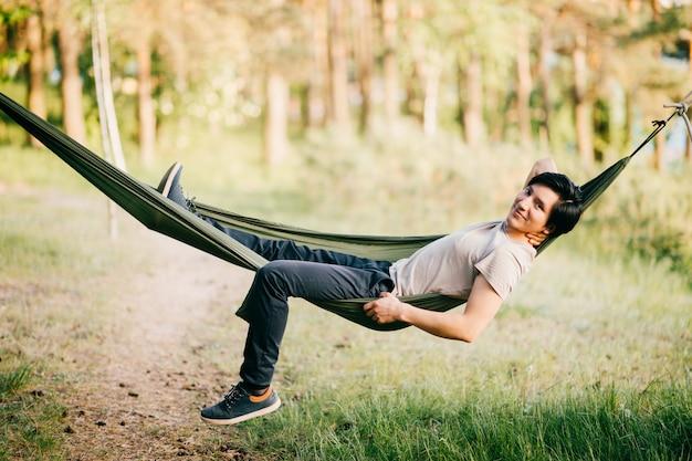 Narive américain jeune homme se détendre dans un hamac dans la nature en journée d'été ensoleillée.