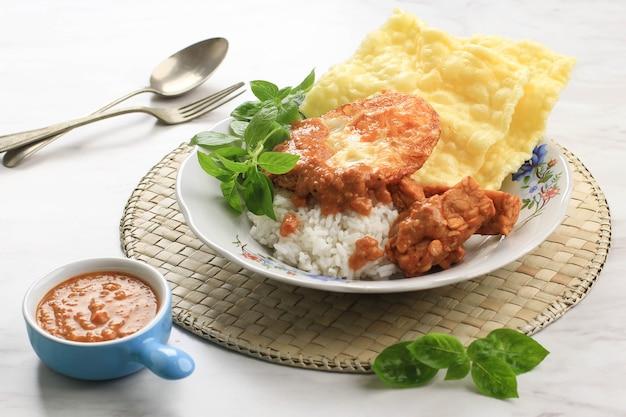 Nasi pecel madiun avec œuf et tempeh frit. pecel est une sauce aux arachides épicée typiquement de java oriental