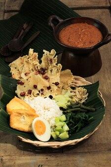 Nasi pecel. plat traditionnel de riz javanais composé de riz cuit à la vapeur avec salade de légumes, vinaigrette à la sauce aux arachides, tempeh, tofu et craquelins peyek. pecel madiun est la variante la plus populaire