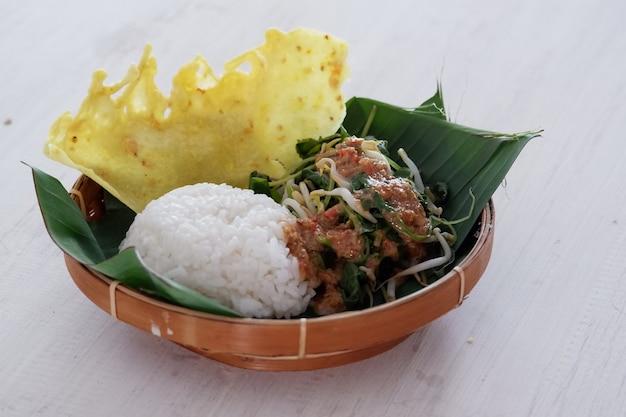 Nasi pecelplat de riz javanais traditionnel de riz cuit à la vapeur avec salade de légumes vinaigrette aux arachides
