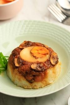 Nasi tim ayam jamur, riz vapeur au poulet sucré et salé avec œuf à la coque sur le dessus.