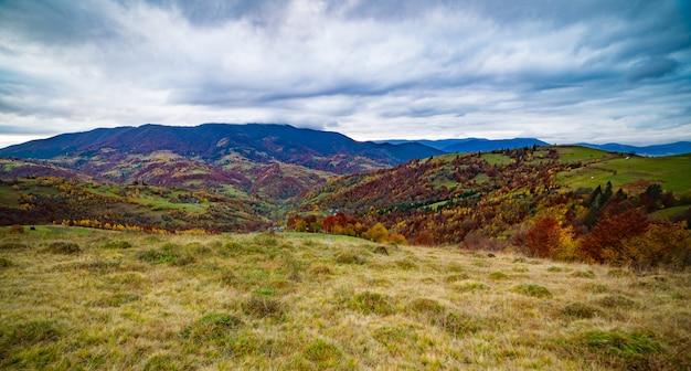 Nature inhabituellement belle des montagnes des carpates dans de belles collines, ciel fantastique de forêts colorées et petit village