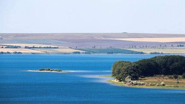 Nature de la moldavie, lac avec petite île, prairie avec arbres luxuriants à droite, larges champs visibles au loin