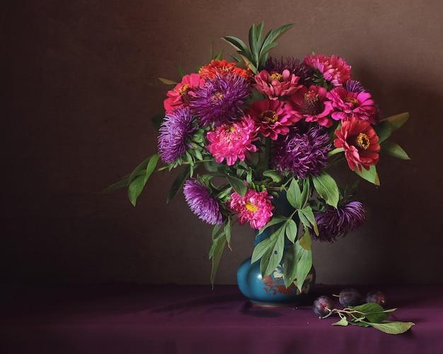 Nature morte avec des asters et des prunes roses et violets.