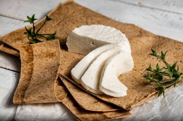 Nature morte au fromage adyghe sur pain pita et feuilles de basilic.