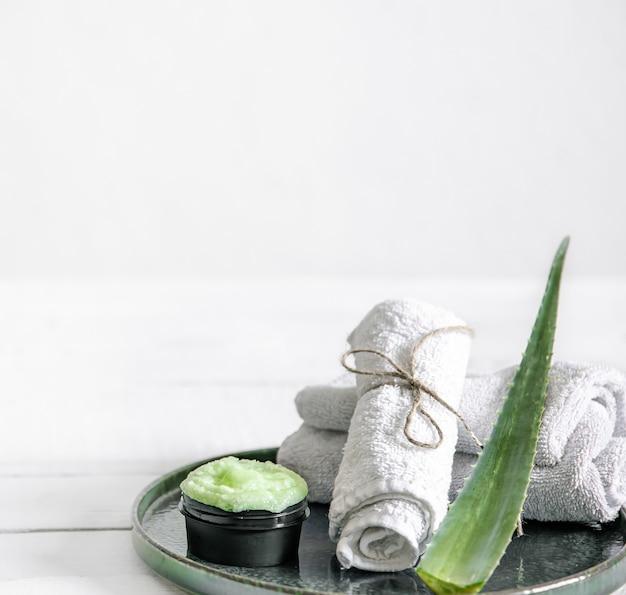 Nature morte au spa avec des soins de la peau bio, des feuilles d'aloès fraîches et des serviettes