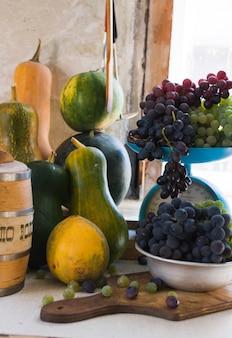 Nature morte d'automne avec citrouilles, melons, pastèque, raisins sur une table blanche en bois.