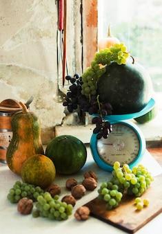 Nature morte d'automne avec citrouilles, noix, melons, pastèque et raisins sur une table blanche en bois.