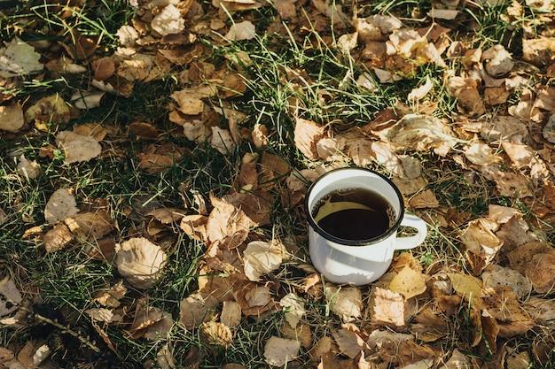 Nature morte d'automne confortable avec tasse en métal avec boisson chaude sur l'herbe et les feuilles jaunes
