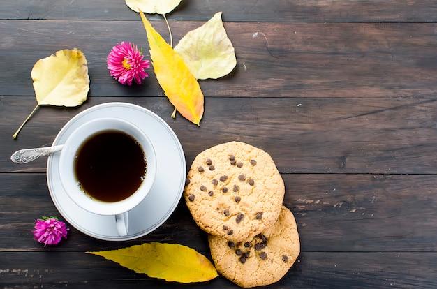 Nature morte d'automne avec tasse de thé, biscuit et feuilles.