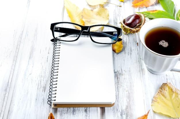 Nature morte d'automne avec une tasse de thé avec des biscuits, un cahier vide, des lunettes et des feuilles