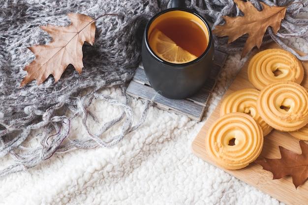Nature morte d'automne avec une tasse de thé, des biscuits, un pull et des feuilles sur une couverture douce et chaude.