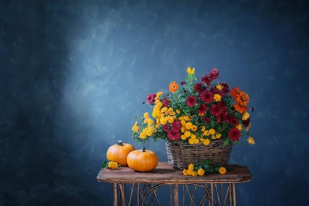 Nature morte aux chrysanthèmes dans un panier et des citrouilles sur une étagère en bois
