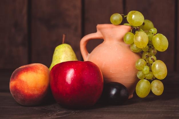 Nature morte aux fruits et pichet sur la table en bois