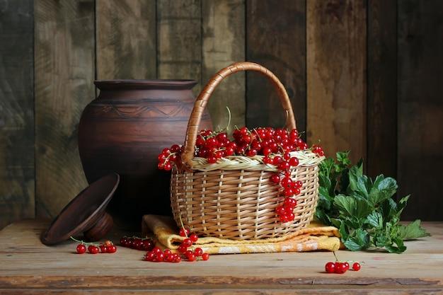 Nature morte aux groseilles rouges dans un panier sur la table dans un style rustique.