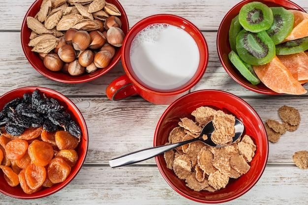 Nature morte aux noisettes, abricots secs, mangue, kiwi et raisins secs sur une surface en bois. mug rouge avec du lait.