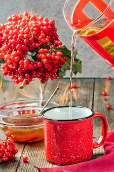 Nature morte baies d'une viorne dans un verre et une tasse de thé chaud et de miel