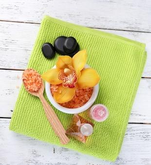 Nature morte avec une belle fleur d'orchidée en fleurs, une serviette et du sel de mer dans un bol sur une table en bois de couleur