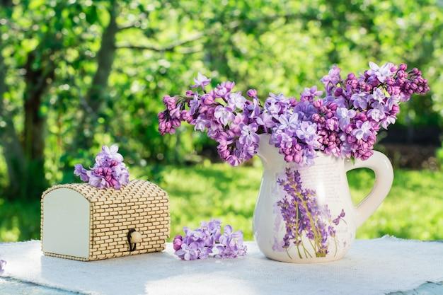 Nature morte avec une boîte lilas sur une serviette de table dans un écrin de verdure