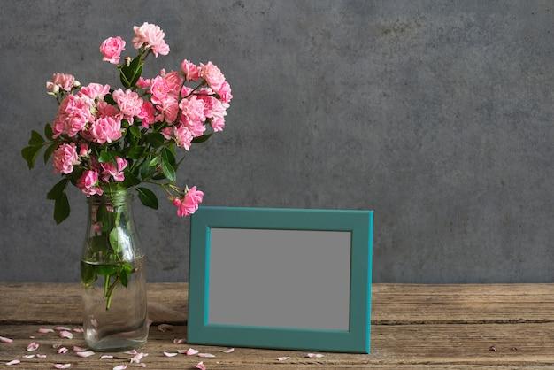 Nature morte avec bouquet de fleurs roses roses, cadre photo vierge et pétales