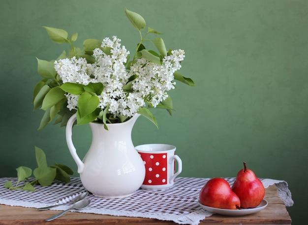 Nature morte avec un bouquet et des fruits dans un style rustique. lilas blanc et poires rouges. fleurs dans un vase.