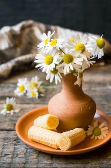 Nature morte d'un bouquet de pâquerettes dans un vase et des tubes de gaufres. style rustique en bois.