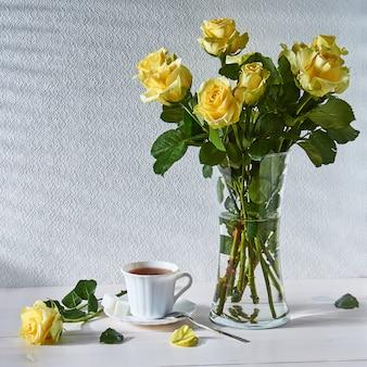 Nature morte avec un bouquet de roses et une tasse de thé