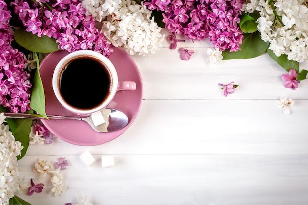 Nature morte avec des branches de lilas et une tasse de café sur une table en bois.