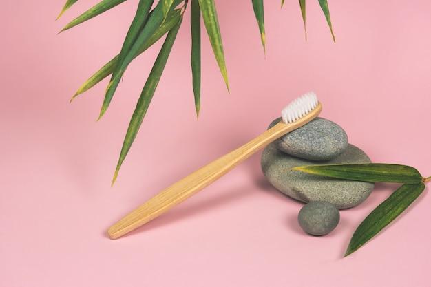 Nature morte avec des brosses à dents en bambou, des pierres et des feuilles de bambou sur fond rose