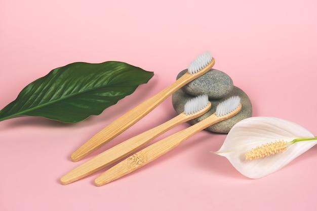 Nature morte avec des brosses à dents en bambou, des pierres et des feuilles vertes sur fond rose