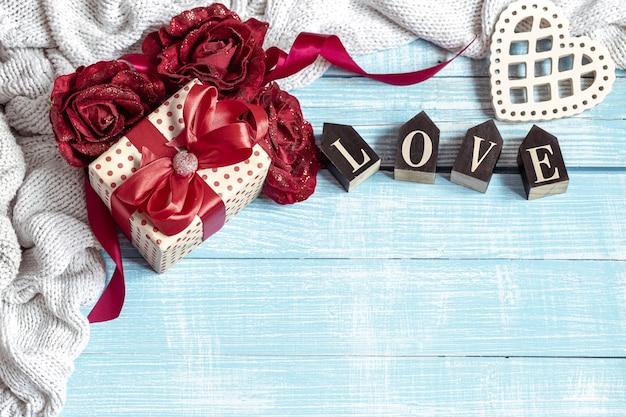 Nature morte avec un cadeau joliment emballé, des fleurs et des éléments décoratifs sur une surface en bois. concept de vacances de la saint-valentin.