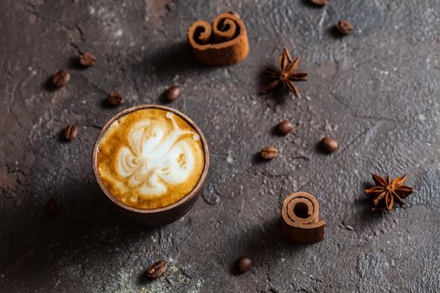 Nature morte de capuccino - art de latte de papillon dans la tasse et les épices d'argile à la main
