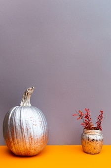Nature morte de citrouille d'or et de brins d'épine-vinette rose-orange sur une table gris-orange