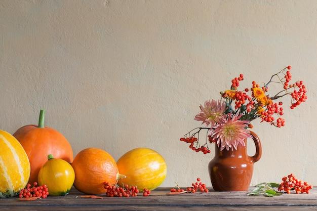 Nature morte avec des citrouilles et des branches de rowan sur table en bois