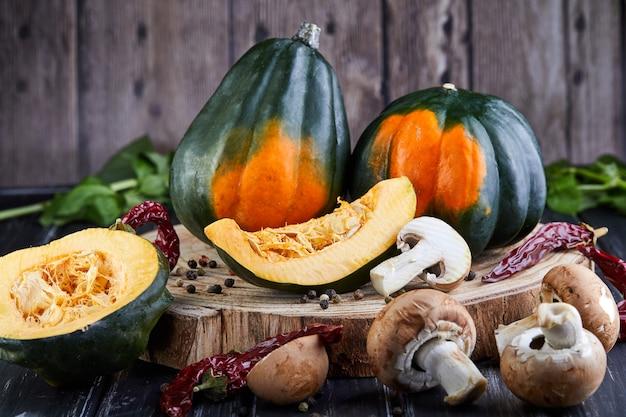 Nature morte de citrouilles vert-orange et citrouille en tranches avec poivron rouge et champignons se trouvant sur un fond en bois foncé