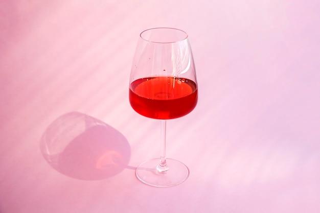 Nature morte avec un cocktail alcoolisé d'été rafraîchissant rouge avec des fraises dans un verre à vin sur fond rose