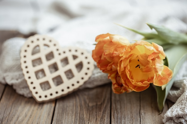 Nature morte confortable avec un cœur décoratif et un bouquet de fleurs se bouchent