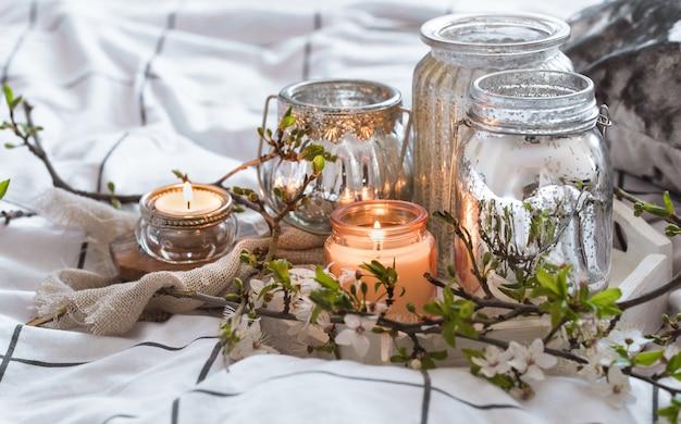 Nature morte confortable avec différentes bougies au lit