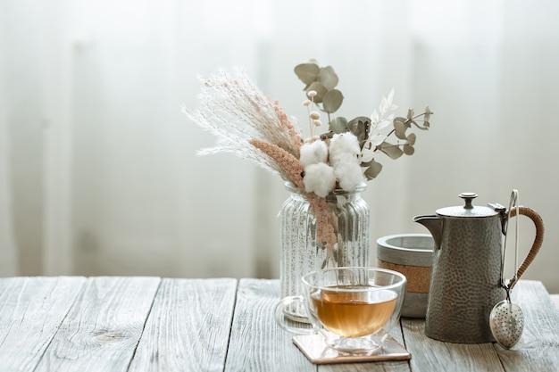 Nature morte confortable avec une tasse de thé en verre, des bougies et un élément tricoté sur un espace de copie d'arrière-plan flou.